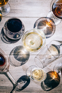 Close-up abstract images of wine glasses filled with red, white and rose wine on table