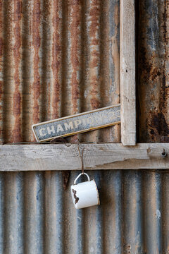 old enamel mug hanging on corrugated iron wall