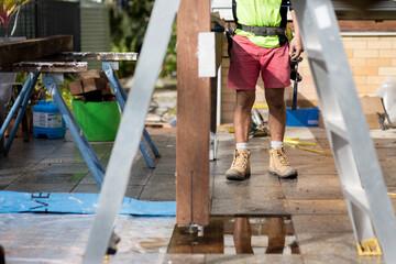 A tradesman standing outside on a home renovation site.