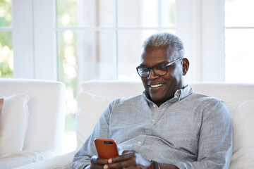 African American Senior man texting on a smart phone sitting on the sofa at home