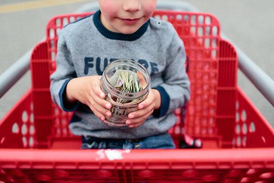 child holding a jar of money