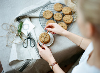 Young woman designing cookies