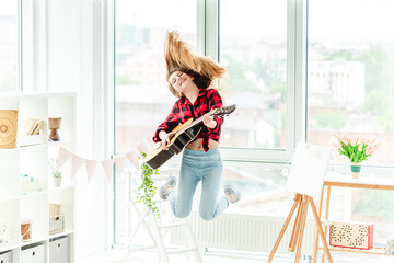 Young girl with guitar in jump