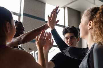 Happy athletes doing high five in gym