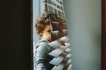 Kid hiding behind the window blinds
