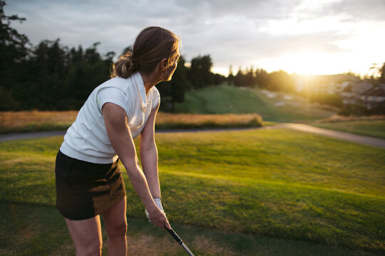 Middle age woman playing golf.