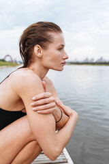 girl in a bathing suit sits on the pier after swimming
