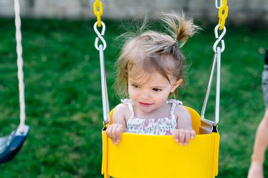 little girl in backyard swing