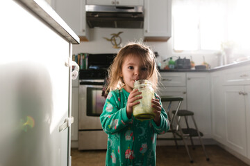 Little girl drinking a green smoothie in kitchen