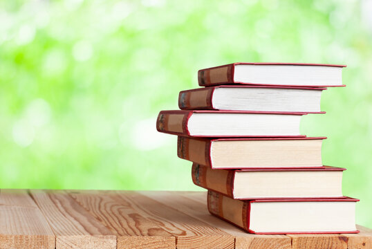 stack of books on the wood table in the nature with bokeh lights
