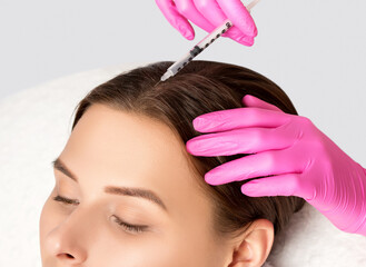 Cosmetologist does prp therapy against hair loss and anti-dandruff of a beautiful brunette woman in a beauty salon. Cosmetology concept.