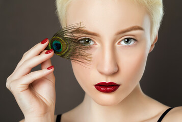 Portrait of a beautiful woman with short blonde hair, beautiful fresh make-up and with feather earrings. Makeup and cosmetology concept.