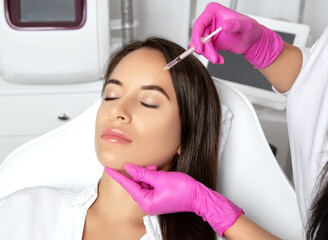 Beautiful brunette woman at the beautician.Cosmetologist does anti wrinkle injections on the forehead and between eyebrows. Women's cosmetology in the beauty salon.