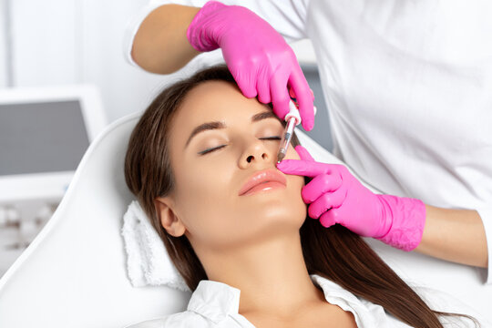 Woman with beautiful clean skin. Cosmetologist does injections for lips augmentation and anti wrinkle in the nasolabial folds of a beautiful woman. Women's cosmetology in the beauty salon.