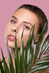 Portrait of a beautiful woman with  brown hair, beautiful fresh make-up and with healthy clean skin with a green leaf on a pink background. Make-up and cosmetology concept.