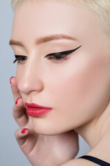 Portrait of a beautiful young woman with short blond hair, beautiful fresh makeup and healthy clean skin on a gray background. The concept of makeup and cosmetology.