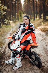 Beautiful young female racer sitting on her motocross bike on a trail of sand in the woods