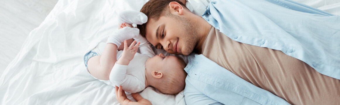 top view of happy father lying on bed face to face with cute baby boy, panoramic shot