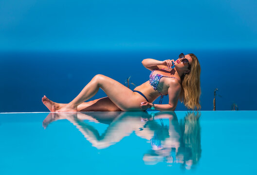 Summer lifestyle in an infinity pool with a young blonde Caucasian woman in a pink and purple bikini with sunglasses. Sunbathing in the pool reflected in the water with the ocean in the background