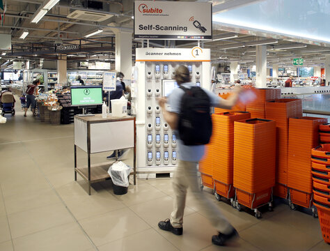 Customer takes a shopping basket at a supermarket of Swiss retail group Migros in Zurich