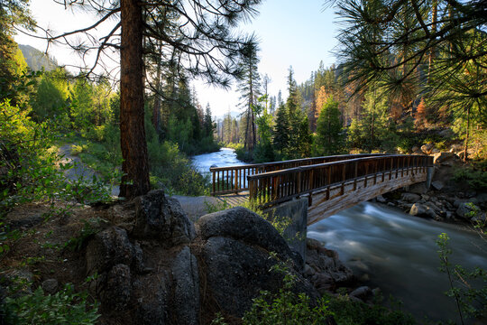 Morning along the Stanislaus River with a foot bridge in the foreground among a wooded forest in Northern California.