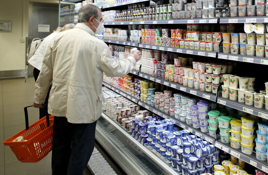 A custumer wears a protective mask as he takes a yogurt at a supermarket of Swiss retail group Migros in Zurich