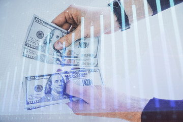 Multi exposure of financial graph drawing hologram and USA dollars bills and man hands. Analysis...