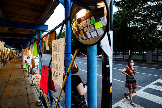 People pass by a scaffolding walkway covered with printed messages and photos in support of the Black Lives Matter movement amid protests on racial inequality at Black Lives Matter Plaza near the White House in Washington