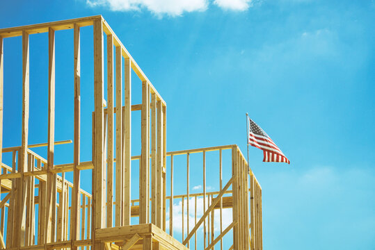 American flag waving in the wind on the top of a construction home framing. Blue sky and white clouds background.