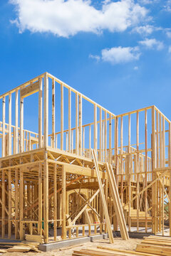 New residential construction home framing. Blue sky and white clouds background.