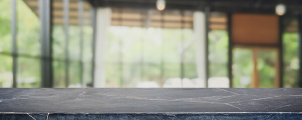 Empty black marble stone table top and blurred coffee shop, cafe and restaurant interior background...