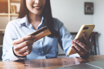 Online payment. Asian woman holding credit card and smartphone for online shopping and payment makes a purchase on the Internet.