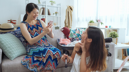 young girl in fashion summer style dress sitting on couch and holding mobile phone taking picture of her friend. female roommate turn around holding brush and showing victory sign looking cellphone