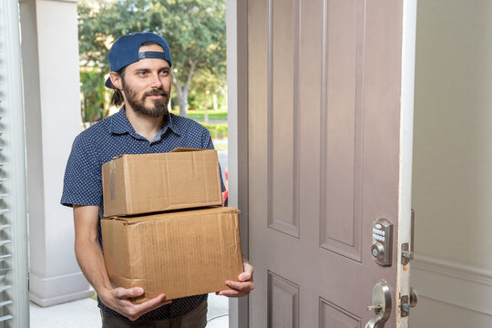 A view of a man entering a home doorway with several boxes of delivery packages.