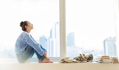 Portrait of beautiful asian woman feeling depress stress in bedroom. Sad face asian girl sit near city view window in winter. Beauty perfect clear skin korean makeup  lifestyle banner (blur)