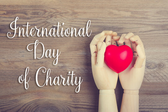 Hand holding red heart on wooden background Top view Flat lay International day of charity concept