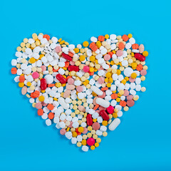 Many pills in the form of a heart Multicolored on a blue background