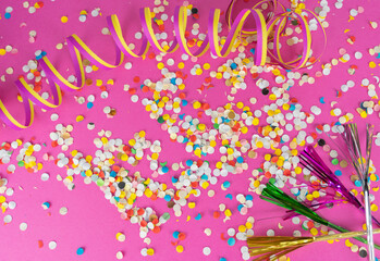 colorful streamers and confetti on pink background