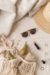 Flat lay, top view neutral fashion composition with women's accessories and bijouterie on beige blanket. String bag, straw hat, sunglasses, lipstick, rings, earrings, pear. Minimal lifestyle concept.