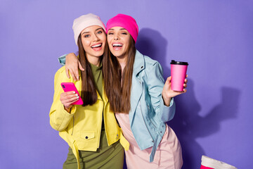 Fototapete - Portrait of nice attractive pretty cheerful girls using cell drinking latte having fun best friends friendship shadow isolated on bright vivid shine vibrant violet lilac purple color background