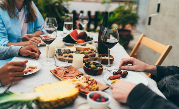 Group of young people dressed in casual clothes dining together drinking red wine and eating snacks, fruits, Friends celebrating birthday sitting in restaurant with small garden enjoying atmosphere