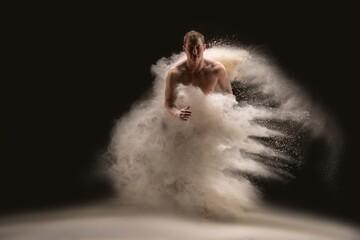Shirtless man dancing in cloud of sand