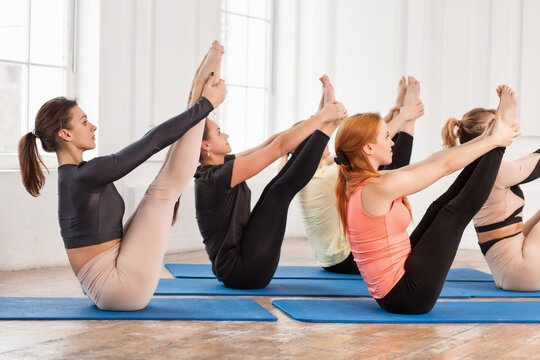 Group of young sporty people doing yoga, up facing dog exercise, Urdhva mukha shvanasana pose, indoor close up, yogi students working out in sport club, studio. Active lifestyle, wellness concept