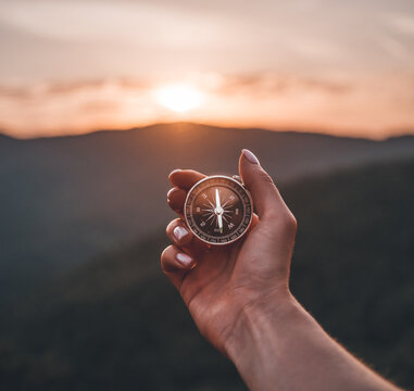 Woman hand with magnetic compass in summer mountains at sunrise, pov.