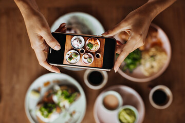 Photo of female hands holding phone and taking pictures of tasty food. Flat-lay. Snapshot of plate with colorful meal