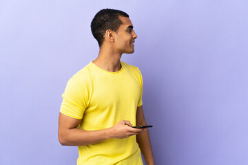 African American man over isolated purple background using mobile phone looking to the side