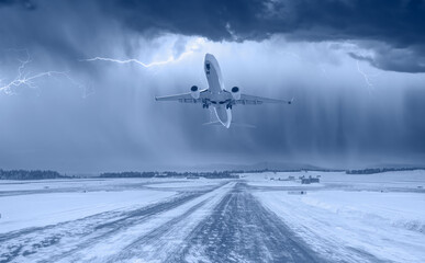 Lightning strikes between stormy clouds - Commercical white airplane fly up over take-off runway the (ice) snow-covered airport-