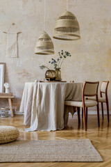 Stylish and elegant dining room interior with diner table, design chairs, rattan pendant lamps, dried flowers in vases, furniture, decoration and elegant personal accessories in cozy home decor.