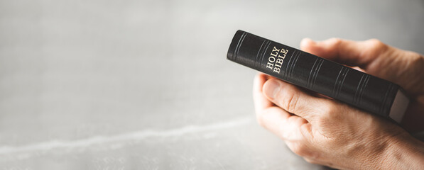 Hands holding Holy Bible over grey background. Sharing the Gospel with youth. Copy space. Christian...