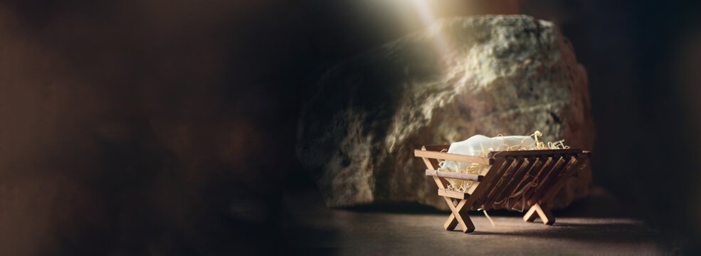 Christian Christmas concept. Birth of Jesus Christ. Wooden manger in cave background. Banner, copy space. Nativity scene symbol. Jesus is reason for season. Salvation, Messiah, Emmanuel, God with us